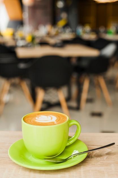 Kopje koffie met creatieve latte kunst op houten tafel in de cafetaria Gratis Foto