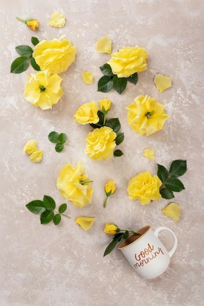 Kopje koffie met de inscriptie goedemorgen en gele rozen en bladeren Premium Foto