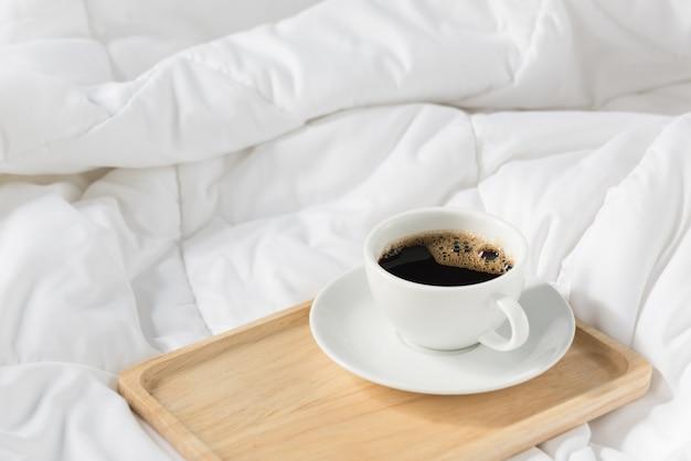 Kopje koffie met houten dienblad op bed Premium Foto