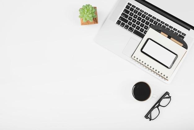 Kopje koffie met laptop; mobiele telefoon en dagboek met pen op witte achtergrond Gratis Foto