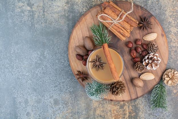 Kopje koffie met pijpjes kaneel en pinecones op houten plaat. hoge kwaliteit foto Gratis Foto