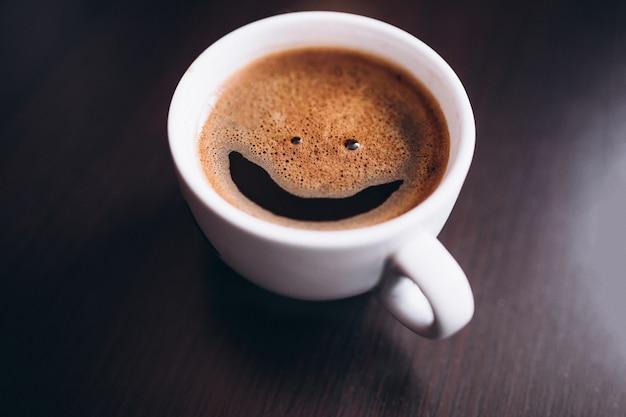 Kopje koffie met schuim, glimlach gezicht, op geïsoleerde bureau Gratis Foto