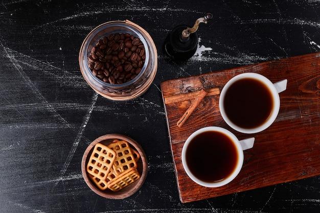 Kopje koffie met smaakkaneeltjes en koekjes. Gratis Foto