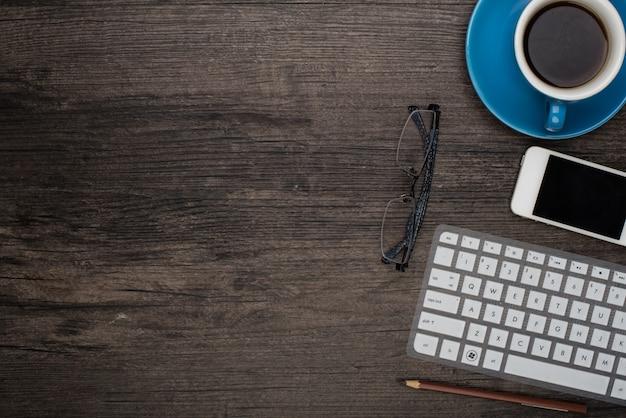 Kopje koffie op een bureau met een laptop en enkele glazen te zien Gratis Foto