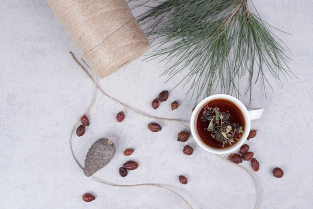 Kopje kruidenthee, gedroogde veenbessen en dennenappel op marmeren tafel. hoge kwaliteit foto Gratis Foto