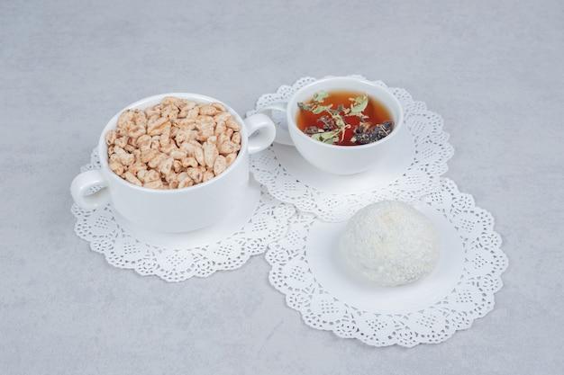 Kopje kruidenthee, kokoskoekje en kom met snoepjes op witte lijst. hoge kwaliteit foto Gratis Foto