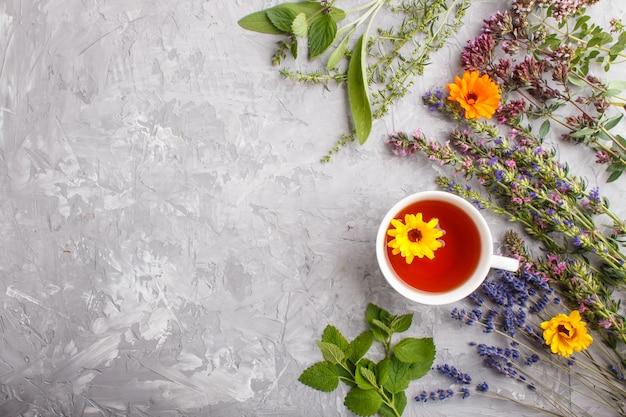 Kopje kruidenthee met calendula, lavendel, oregano, hysop, munt en citroenmelisse. bovenaanzicht, achtergrond copyspace. Premium Foto