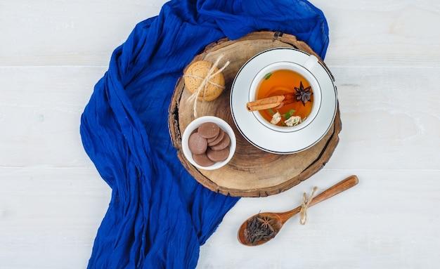 Kopje thee, bruine en witte koekjes op houten bord met blauwe sjaal en een lepel kruidnagel Gratis Foto