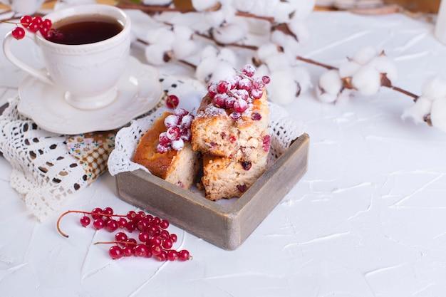 Kopje thee en schotel, cupcake met rode bessen op een houten bord en witte achtergrond, katoen bloemen Premium Foto