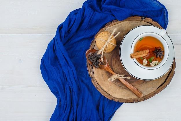Kopje thee, kruidnagel en koekjes op houten bord met blauwe sjaal Gratis Foto
