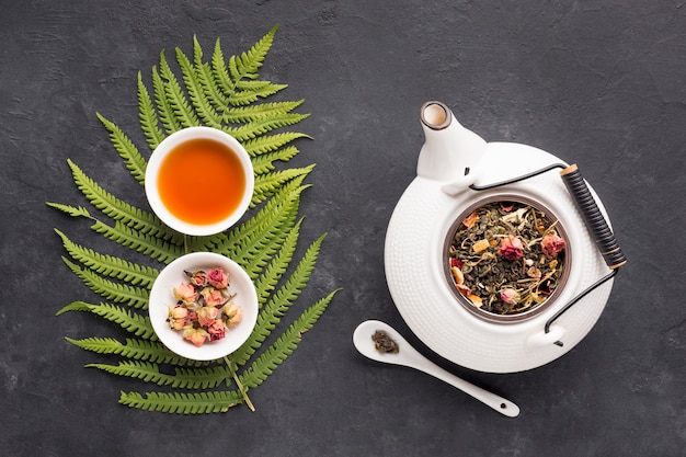 Kopje thee met aromatische droge thee in kommen op zwarte stenen achtergrond Gratis Foto