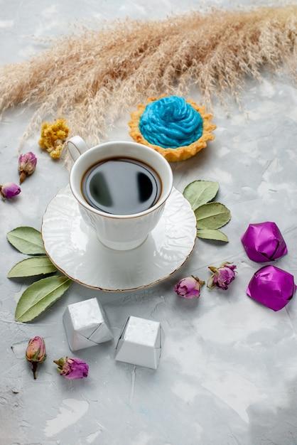 Kopje thee met blauwe crème cake chocolade snoepjes op wit-grijs bureau, koekje zoete thee snoep chocolade Gratis Foto