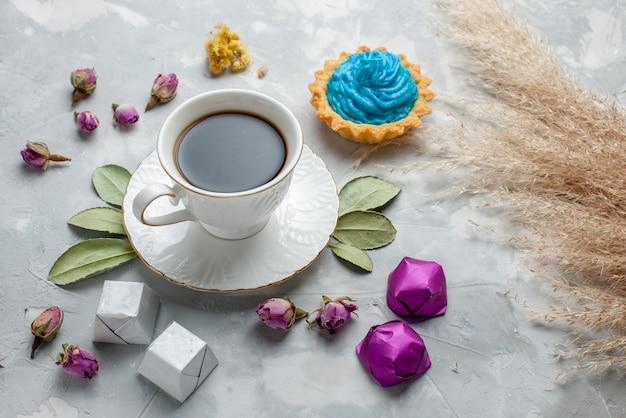 Kopje thee met blauwe crème taart chocolade snoepjes op wit-grijs, koekje zoete thee snoep Gratis Foto