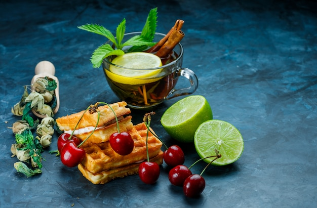 Kopje thee met munt, kaneel, gedroogde kruiden, kersen, limoen op grungy blauwe oppervlak, hoge hoek bekeken. Gratis Foto