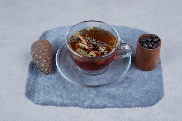 Kopje thee, pinecone en korrels op marmeren achtergrond. hoge kwaliteit foto Gratis Foto
