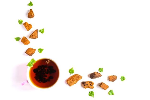 Kopje thee van berkchaga-paddenstoel en gemalen chaga-schimmelstukken voor het brouwen van thee geïsoleerd op een witte achtergrond. ruimte voor tekst Premium Foto