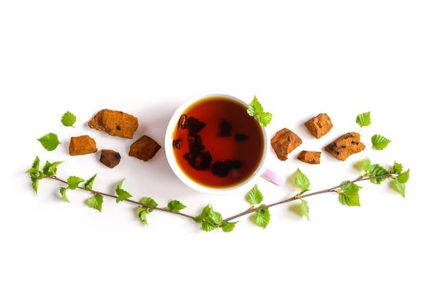Kopje thee van berkchaga-paddenstoel en gemalen chaga-schimmelstukken voor het zetten van thee geïsoleerd op een wit oppervlak Premium Foto