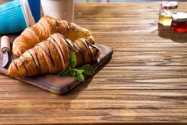Kopjes koffie en twee croissants op straat in croissant cafe Premium Foto