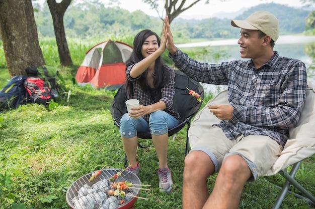 Koppel high five terwijl u geniet van kamperen Premium Foto
