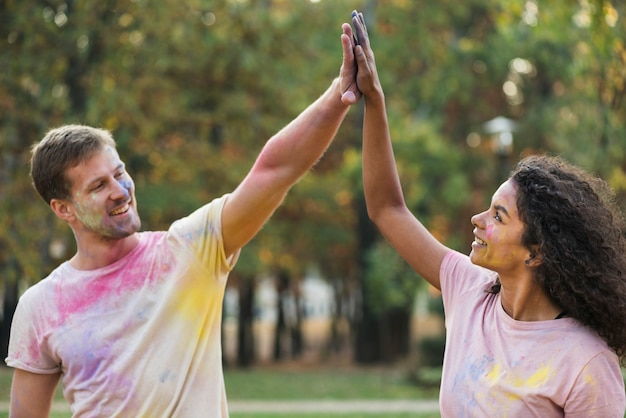 Koppel high-fiving elkaar bij holi Gratis Foto
