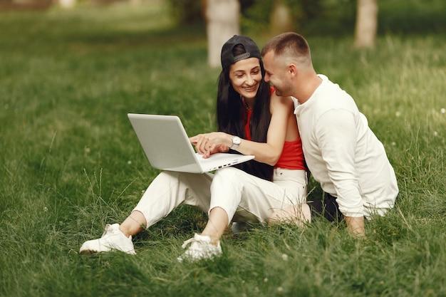 Koppel in een lentestad. dame met een laptop. mensen zitten op een gras. Gratis Foto