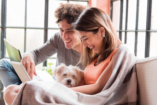 Koppel met hond thuis werken Gratis Foto