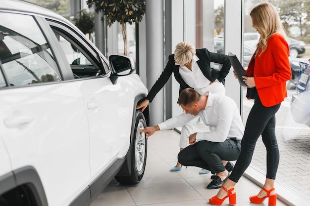 Koppel vervolgens een auto aan te raken wiel en aandachtig ernaar te kijken. vrouw en man kiezen een auto Premium Foto