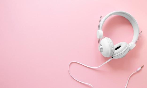 Koptelefoon op roze achtergrond met exemplaar-ruimte Premium Foto