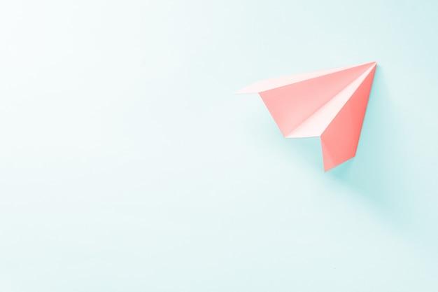 Koraal papieren vliegtuigje op een lichtblauwe achtergrond. trendy 2019 kleurenconcept Premium Foto