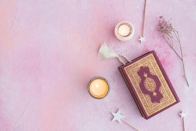 Koran en kaarsen op roze Gratis Foto