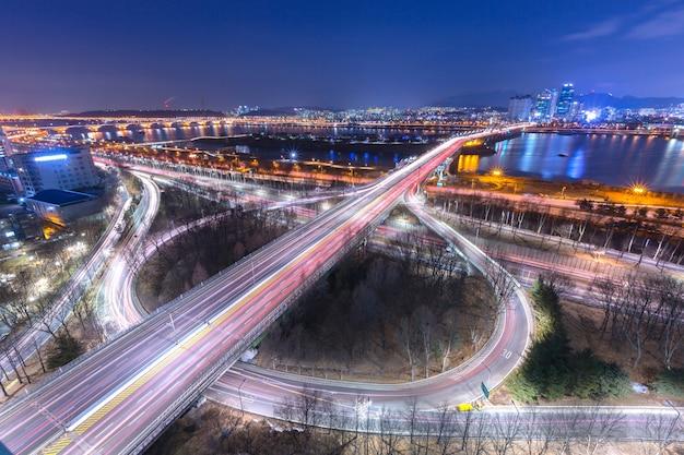 Korea reizen, auto's passeren in kruising, han rivier en brug 's nachts in het centrum van seoul, zuid-korea. Premium Foto