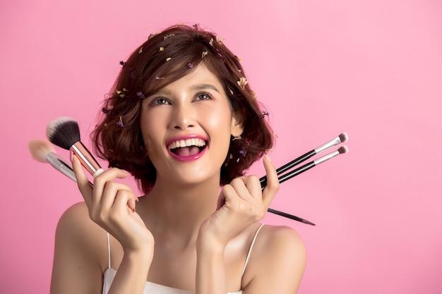 Korte haar aziatische jonge mooie vrouw die kosmetische poederborstel toepassen Gratis Foto
