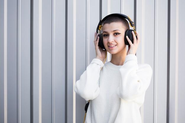 Kortharige vrouw die aan muziek met hoofdtelefoons luistert Gratis Foto