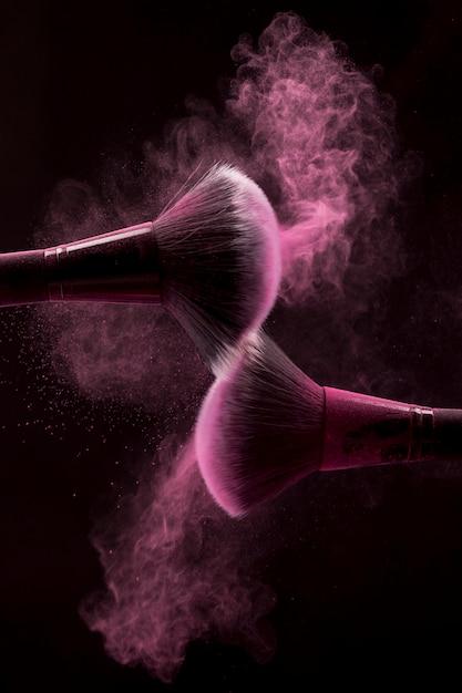 Kosmetische borstels in roze mist van poeder op donkere achtergrond Gratis Foto