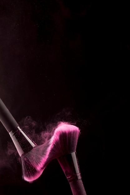 Kosmetische borstels in stof van poeder op donkere achtergrond Gratis Foto