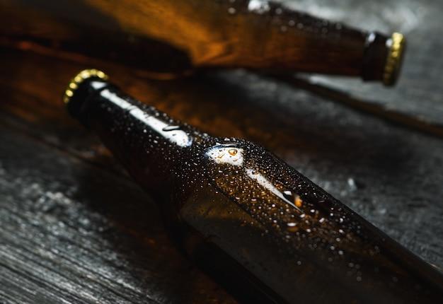 Koud biertje in glazen flessen op houten tafel Premium Foto