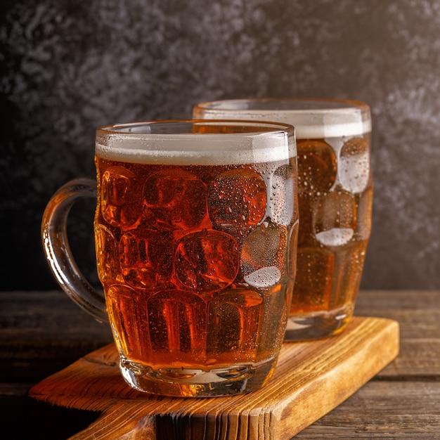 Koud biertje in glazen pinten op een houten bord Premium Foto