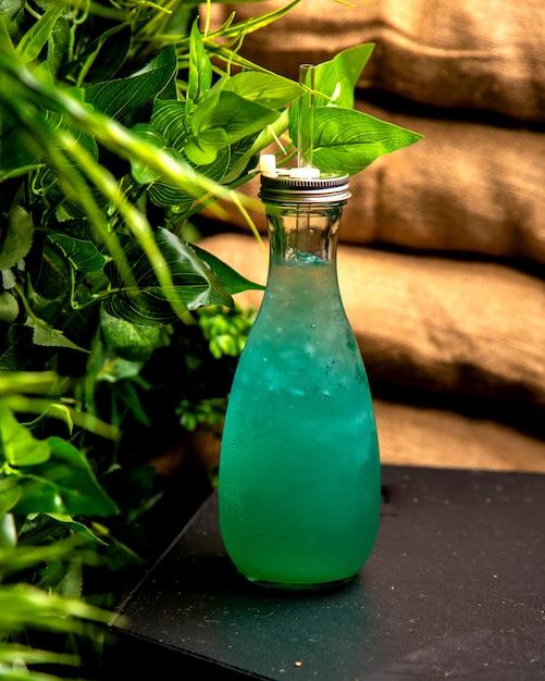 Koud drankje met ijs turquoise in een glazen fles Gratis Foto