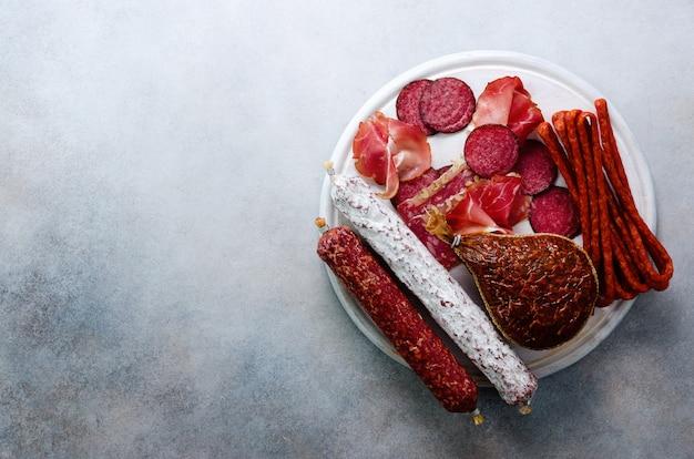 Koud gerookte vleesplaat. traditionele italiaanse antipasto, snijplank met salami, prosciutto, ham, varkenskarbonades, olijven op grijs. Premium Foto