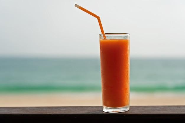 Koud het sapglas van het papajafruit met buisje op het oceaanstrand. Premium Foto