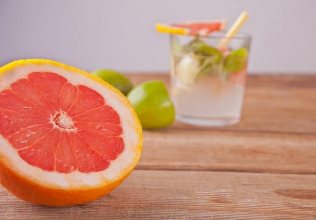 Koud sap met roze grapefruit, limoen en muntblaadjes op houten tafel Premium Foto