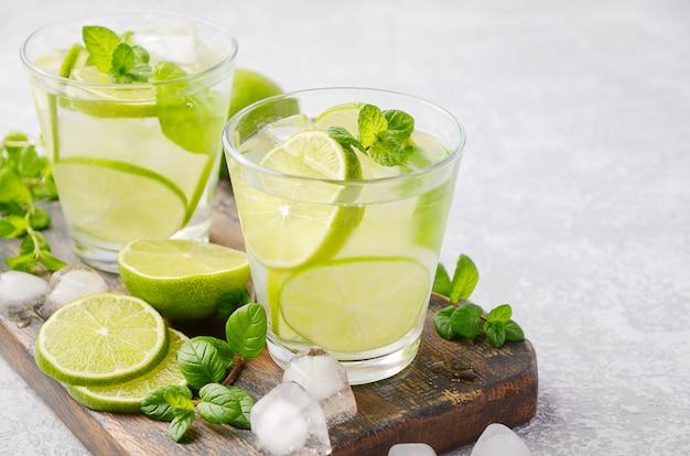 Koud verfrissende zomerdrank met limoen en munt in een glas op een grijze betonnen of stenen tafel. Premium Foto