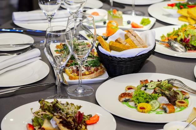 Koude voorgerechten en salades op een dienende tafel Premium Foto