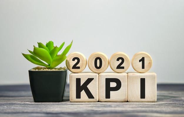 Kpi 2021 - financieel concept. houten blokjes en bloem in een pot. Premium Foto