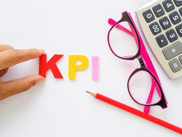Kpi-alfabet met rood potlood en roze glazen gezet op witte lijstachtergrond Premium Foto
