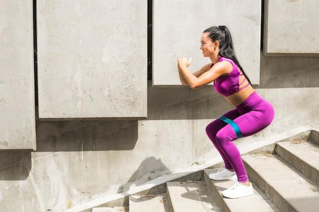 Kraakpanden. weerstandsband sportieve jonge vrouw doet squat oefening met buit band stretching riem. fitness vrouw traint rubber Premium Foto