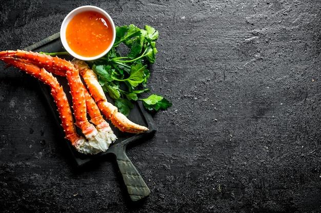 Krab op een snijplank met peterselie en saus. op zwarte rustieke ondergrond Premium Foto