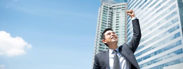 Krachtige aziatische zakenman die overwinning toont, die, buiten het bureau machtigt - panoramische banner Premium Foto