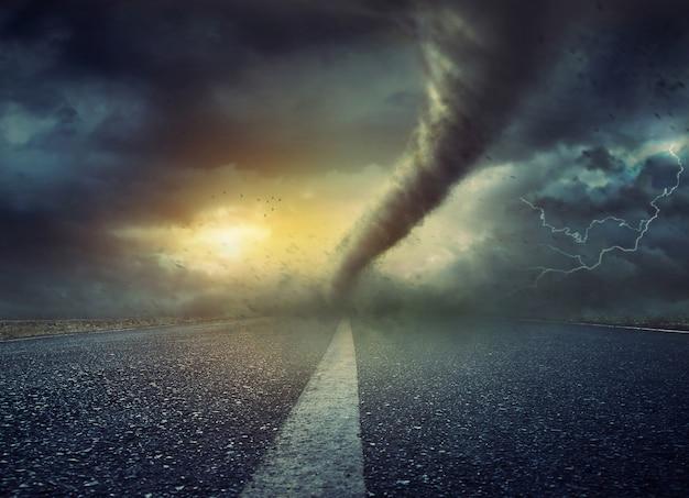 Krachtige enorme tornado die op de weg draait Premium Foto