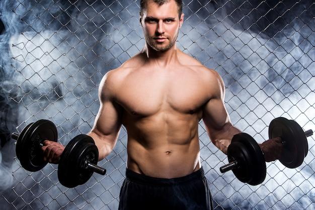 Krachtige kerel met domoren die spieren op omheining tonen Gratis Foto